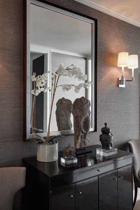 Foyer with grasscloth contemporary sconces and mirror with asian antiques open living dining room floor plan in a chicago high rise apartment