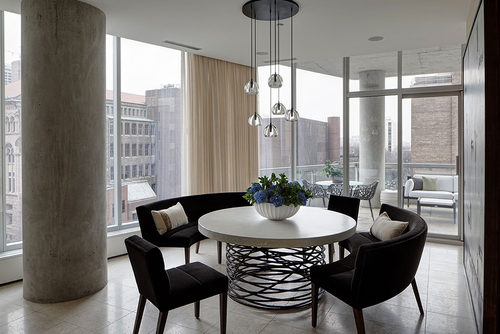 Concrete dining table with banquette seating and contemporary glass light fixture